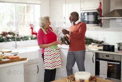 Senior black couple opening champagne and laughing together in the kitchen