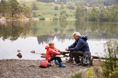 Grandfather and grandson sitting at the shore of a lake talking, elevated view, Lake District, UK