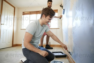 Two Men Decorating Room In New Home Painting Wall Together