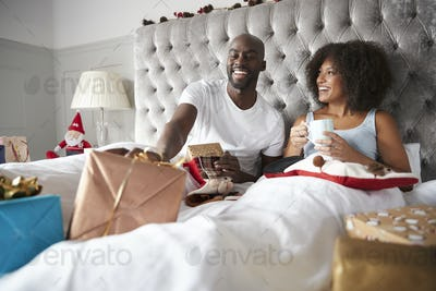 Happy young black couple sitting in bed giving gifts to each other on Christmas morning, low angle