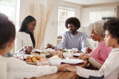 Multi generation mixed race family holding hands and saying grace before eating their Sunday dinner