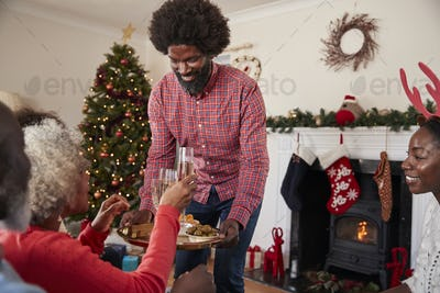Man Serving Champagne And Snacks As Adult Members Of Family Celebrate Christmas At Home