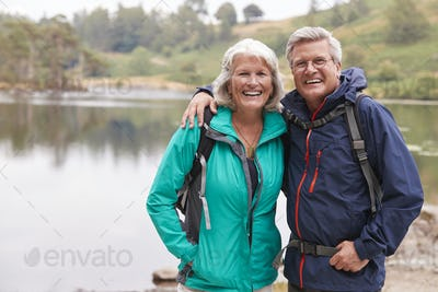 Happy senior couple standing on the shore of a lake smiling to camera, Lake District, UK