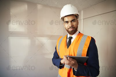 Portrait Of Surveyor With Digital Tablet Carrying Out House Inspection