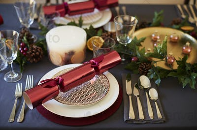 Close up of Christmas table setting with crackers arranged on plates