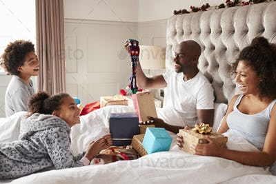 Dad sitting up in bed opening a gift on Christmas morning watched by his family, close up