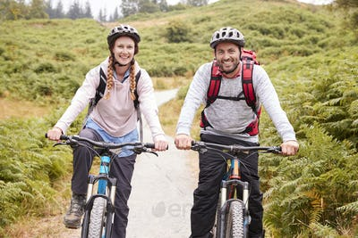 Young adult couple riding mountain bikes in a country lane, looking at camera, close up
