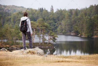 Young adult woman standing on a rock admiring the view of a lake, back view, Lake District, UK
