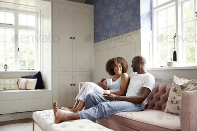 Young black couple sitting together on couch in living room drinking coffee and talking