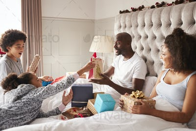 Young mixed race family sitting on parents bed giving each other gifts on Christmas morning