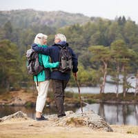 Senior couple embracing and admiring a view of lakes looking at each other, back view