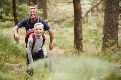 Grandfather and grandson hiking in a forest amongst greenery, front view