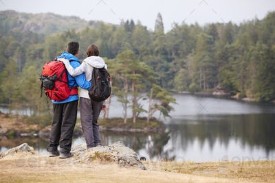 Young adult couple standing on a rock admiring the lakeside view, back view