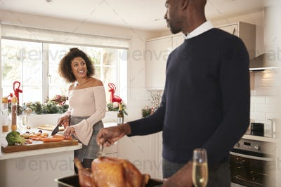 Young adult mixed race couple preparing Christmas dinner together at home