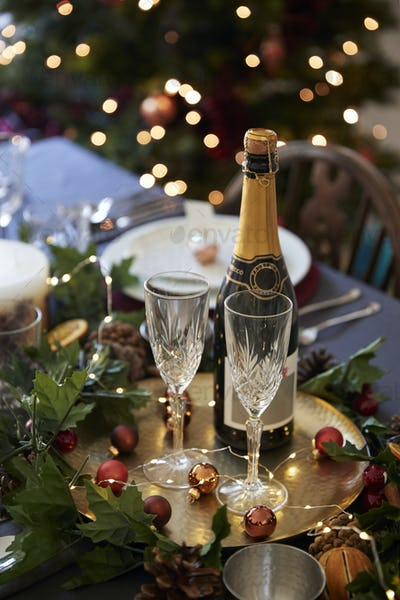 Christmas table setting with glasses and a bottle of champagne, baubles arranged on a gold plate