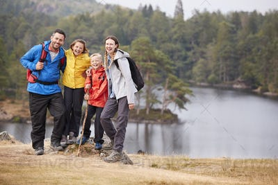 Young family standing on a rock by a lake looking to camera embracing, full length