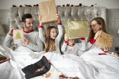 Excited Family In Bed At Home Opening Gifts On Christmas Day