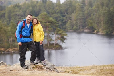 Caucasian pre-teen girl standing with her father on a rock by a lake, smiling to camera