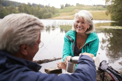 Senior couple by a lake, man pouring coffee to his wifeÕs cup, over shoulder view, Lake District, UK