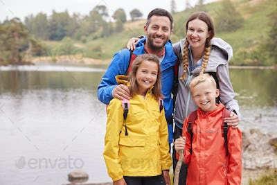 Young family standing on the shore of a lake in the countryside looking to camera