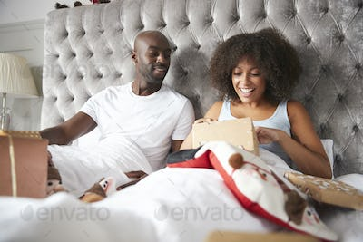 Young adult black couple opening gifts in bed on Christmas morning, low angle