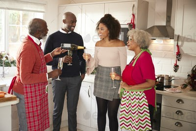 Senior black man pouring champagne for his family to celebrate while preparing Christmas dinner