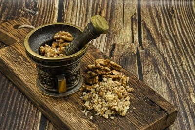 Walnuts in a metal mortar with pestle