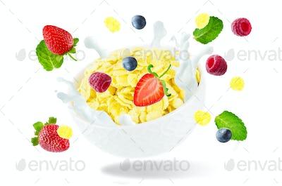 Healthy breakfast with milk, flying corn flakes, raspberries, st