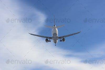 Airplane flies against a background of white cloud