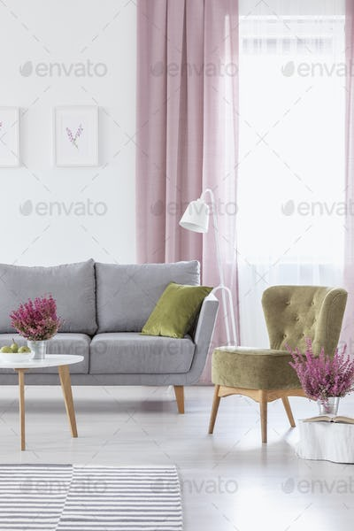 Vertical view of elegant living room with grey comfortable couch