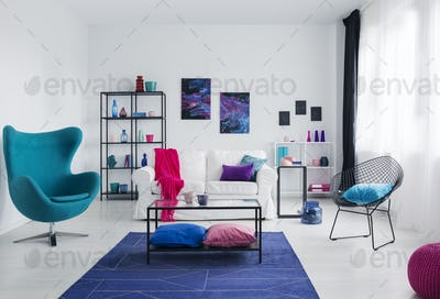 Table on navy blue carpet in white apartment interior with armch
