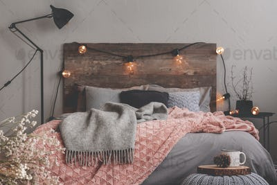 Grey and pastel pink blanket on grey bedding of fashionable bedr