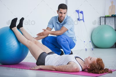 Professional physiotherapist and sportswoman on mat exercising w