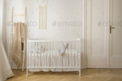 Scandinavian nursery with white wooden crib and macrame on the w