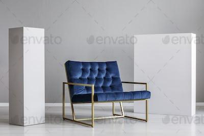 Velvet petrol blue armchair between two white blocks of wood