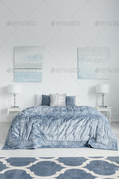 Stylish bedroom design with king size bed, white bedside tables