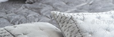 Panorama and close-up on elegant grey pillows with decorative tr