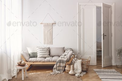 Living room with stylish macrame, sofa, wooden accessories and d