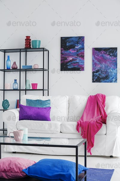 Pink blanket on white sofa in cosmos living room interior with t