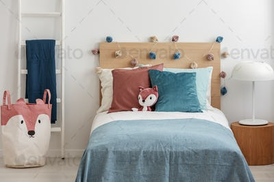 Plush fox on singe bed with colorful pillows and duvet