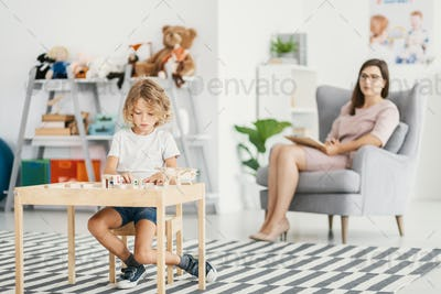 Boy playing at desk in the classroom while psychologist analysin