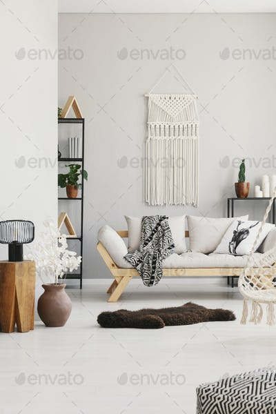 Vertical view of cozy living room with stylish couch with pillow