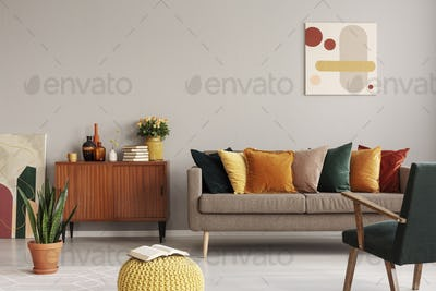 Abstract painting on grey wall of retro living room interior wit