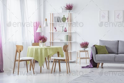 Elegant living room with wooden chairs, round table with olive g