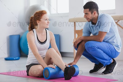Ginger girl working out with her trainer using a foam roller