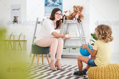 Smiling teacher playing with child with blue ball in the school