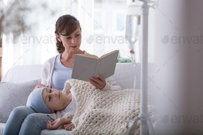 Mother reading book to weak child with leukemia during treatment