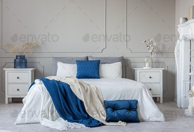 Grey, white and blue pillows and blanket on king size bed in ele