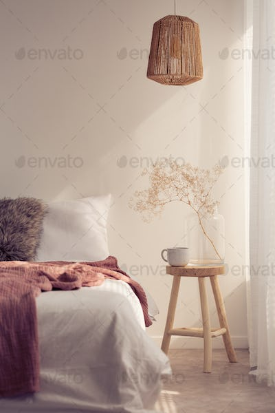 Bedside table with mug and flower next to bed with white bedding