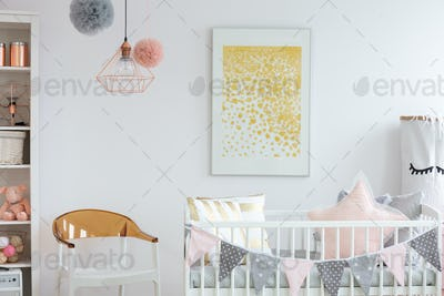 Stylish white and brown chair next to crib with pillows in trend